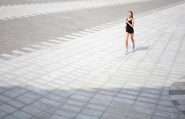 Young woman running in city copy space - Stock Photo - Images