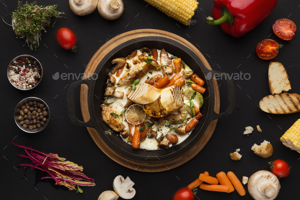 Chicken and vegetables stewed in pot on black background - Stock Photo - Images