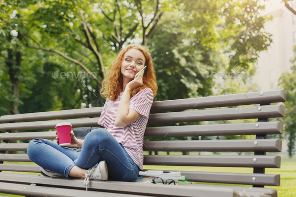 Beautiful student sitting and talking on the phone outdoors - Stock Photo - Images