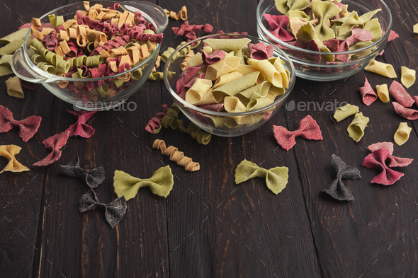 Various colorful pasta in glass bowls on wooden background - Stock Photo - Images