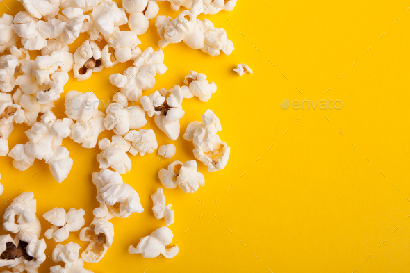Slaty popcorn scattered on yellow background, top view - Stock Photo - Images