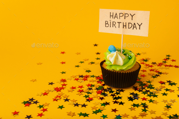 Birthday cupcake with greeting card on yellow background - Stock Photo - Images