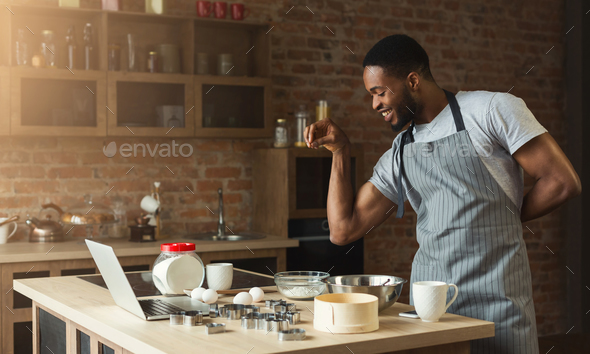 African-american man baking cookies at home kitchen - Stock Photo - Images