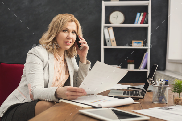 Successful businesswoman at work talking on phone - Stock Photo - Images