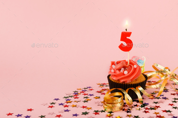 Fifth birthday cupcake with candle and sprinkles - Stock Photo - Images