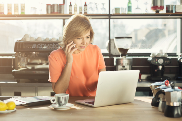 Middle-aged woman barista working on laptop and talking on smartphone - Stock Photo - Images