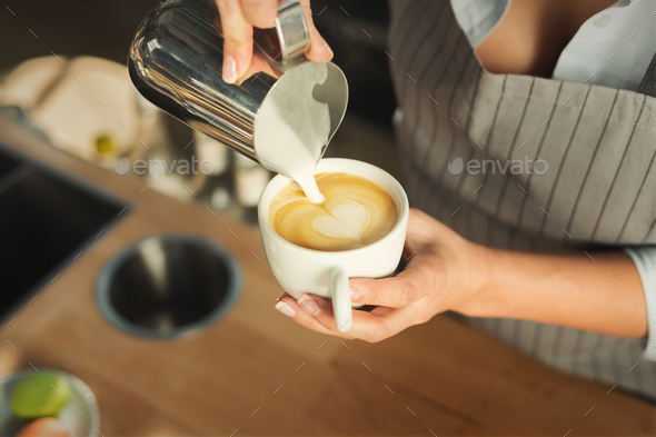 Closeup of barmen pouring milk to cappuccino cup - Stock Photo - Images