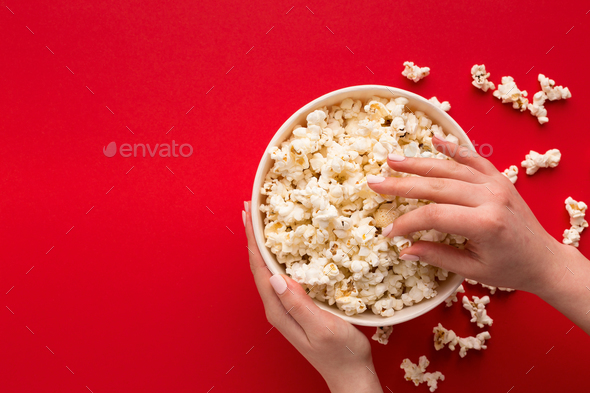 Bucket of popcorn on red background, top view - Stock Photo - Images