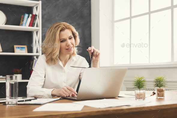 Serious businesswoman working on laptop at office - Stock Photo - Images