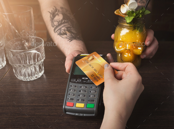 Woman paying for cocktail with credit card at bar counter - Stock Photo - Images