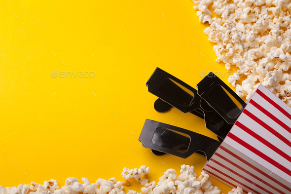 3D glasses and popcorn on yellow background - Stock Photo - Images