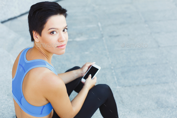 Female runner with smartphone on stairs - Stock Photo - Images