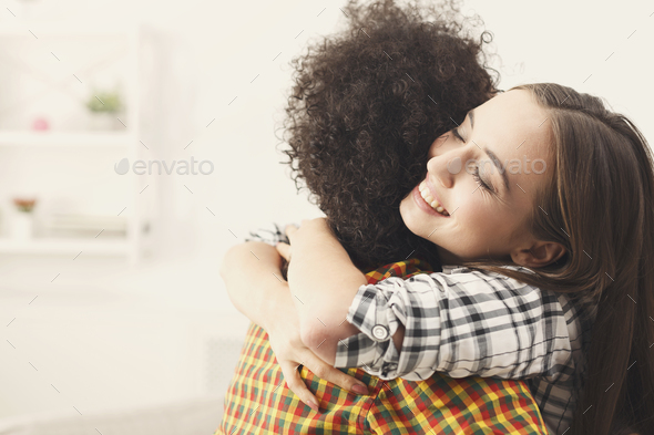 Two female friends embracing each other at home - Stock Photo - Images