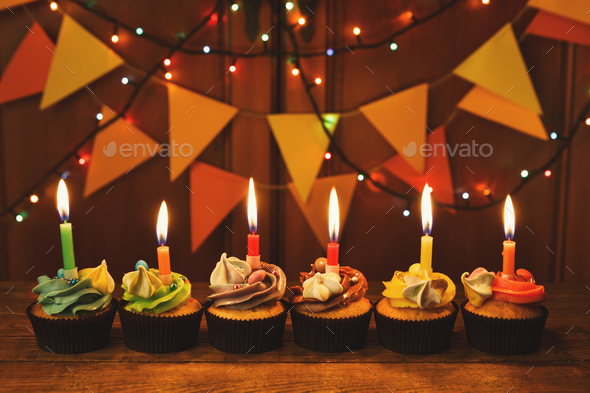 Chocolate cupcakes with candles against festive background - Stock Photo - Images