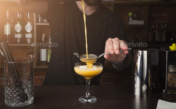 Hands of barman preparing cocktail at bar counter - Stock Photo - Images