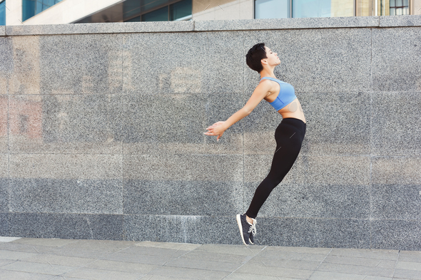 Beautiful young woman jumping against brick wall - Stock Photo - Images