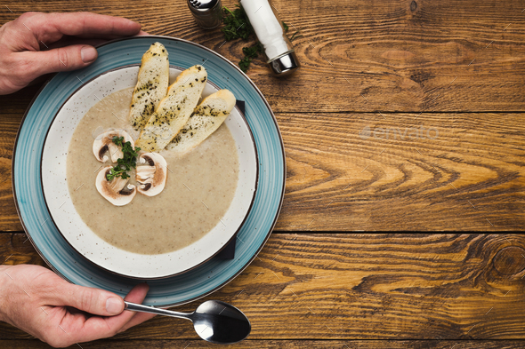 Male hands with mushroom cream soup, top view - Stock Photo - Images