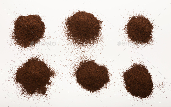 Heaps of brown ground coffee beans isolated on white - Stock Photo - Images