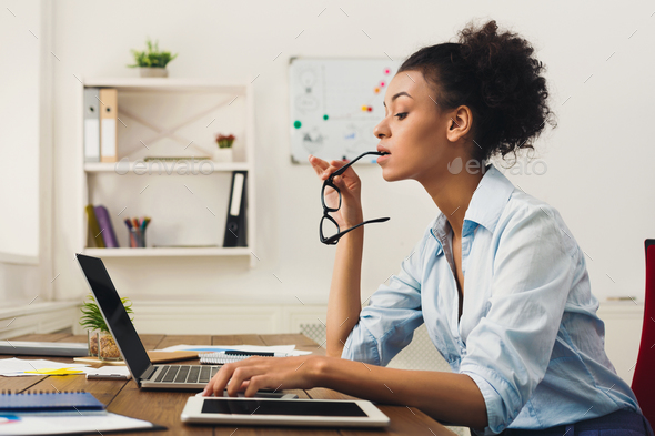 Serious business woman working on laptop at office - Stock Photo - Images