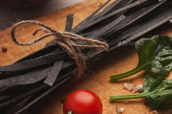 Pile of black colored fettuccine pasta on wood, closeup - Stock Photo - Images