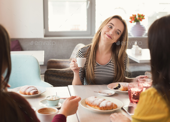 Happy female frinds drinking coffee and chatting at cafe - Stock Photo - Images