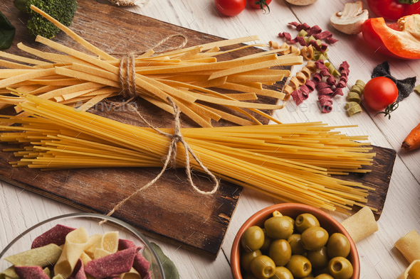 Pasta and cooking ingredients on white wood - Stock Photo - Images