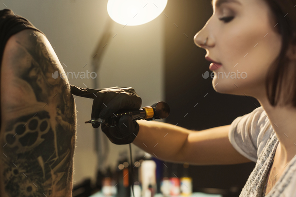 Young woman tattooist doing tattoo on shoulder - Stock Photo - Images
