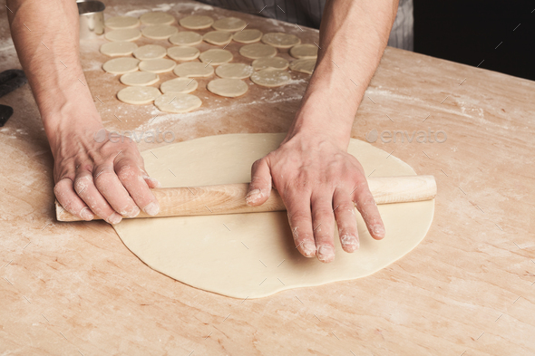Preparing dumplings with meat, rolling out dough - Stock Photo - Images
