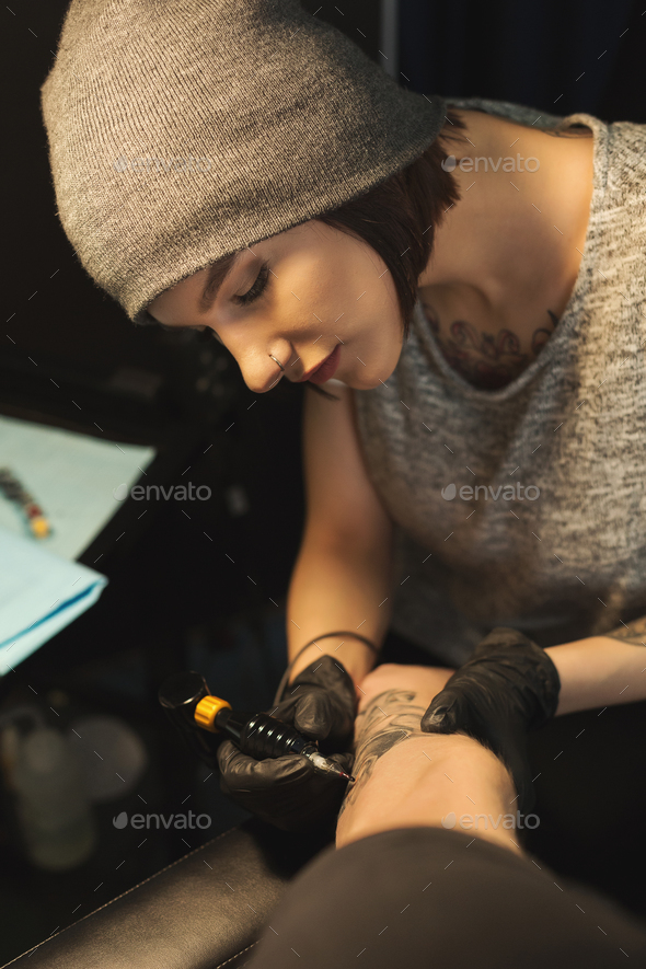 Young woman tattooist doing tattoo on male arm - Stock Photo - Images