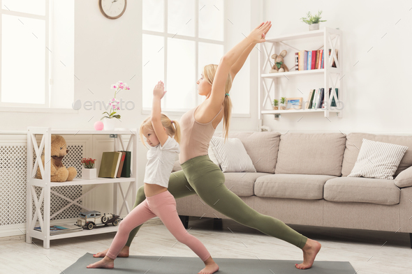 Mother and little daughter doing yoga together - Stock Photo - Images