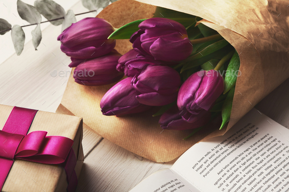 Bouqet of purple tulips and gift box on wooden background - Stock Photo - Images