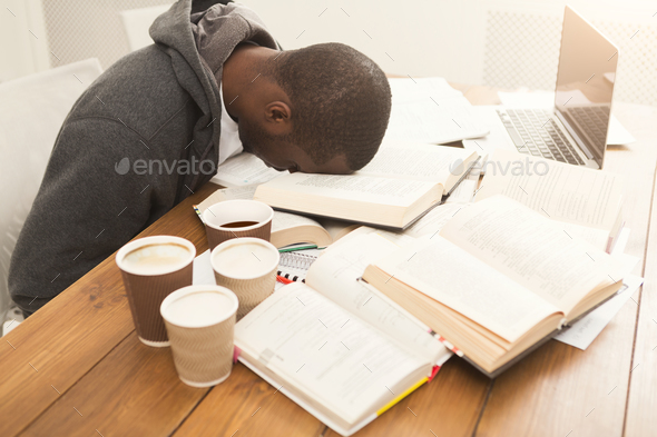Black male student studying at table full of books - Stock Photo - Images
