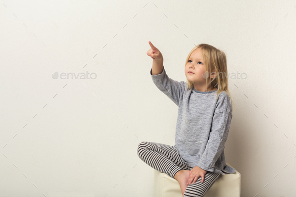 Happy little girl pointing aside at white studio - Stock Photo - Images