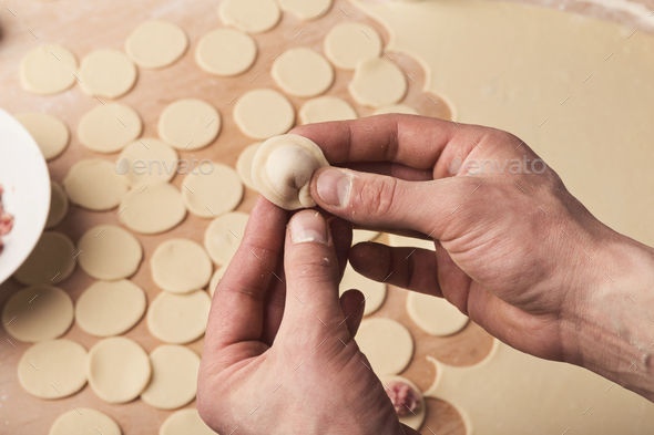 Preparing dumplings with meat, forming small ravioli - Stock Photo - Images