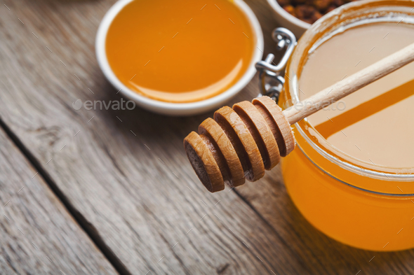 Closeup of liquid honey on wooden background - Stock Photo - Images