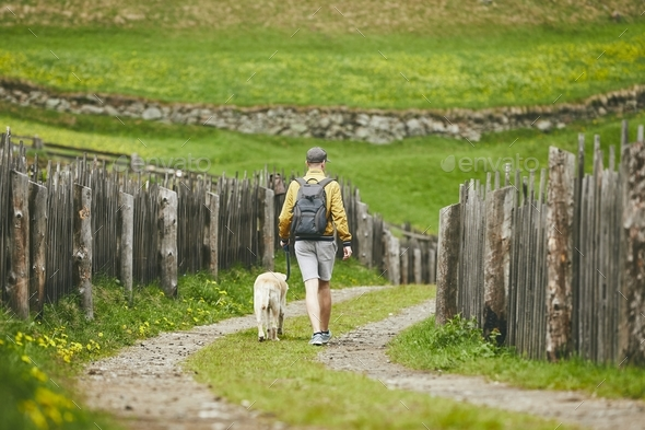 Tourist with dog in countryside - Stock Photo - Images