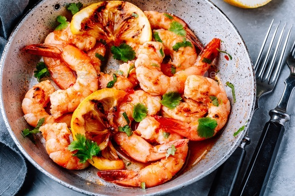Spicy garlic chilli Shrimps on frying pan with lemon and cilantro - Stock Photo - Images