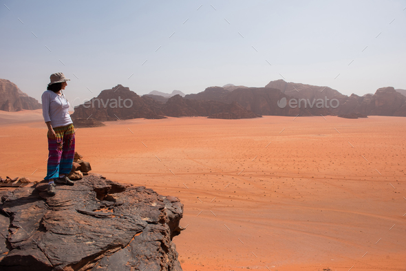 Woman admiring desert landscape on a cliff - Stock Photo - Images