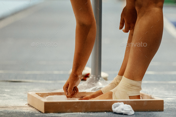 female gymnast rubs chalk on his legs - Stock Photo - Images