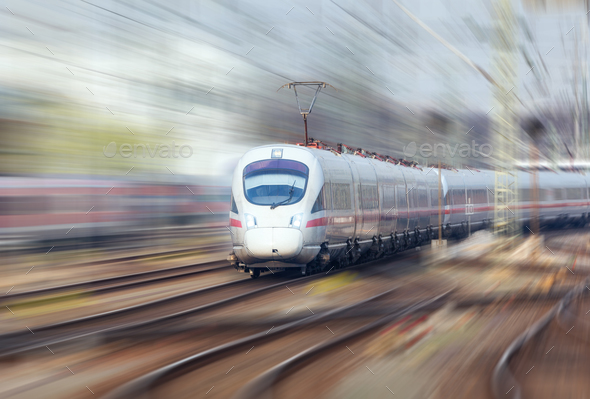 Railway station with modern white train at sunset - Stock Photo - Images