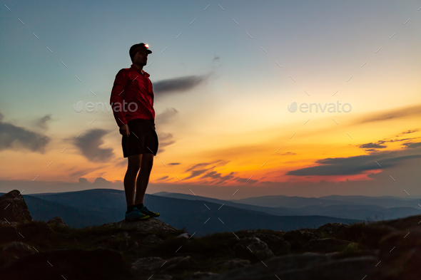 Trail runner with head lamp on top of mountain peak at night. - Stock Photo - Images