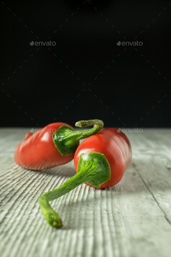Red chili peppers on a rustic wooden surface - Stock Photo - Images