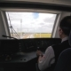 Machinist Drives Train in Cabin Among Yellow Fields