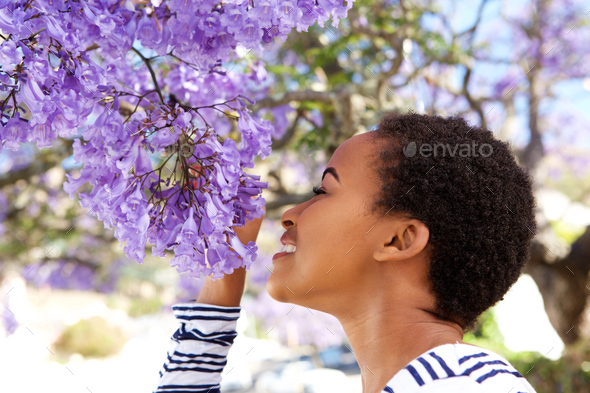 young black woman smelling flowers on tree - Stock Photo - Images