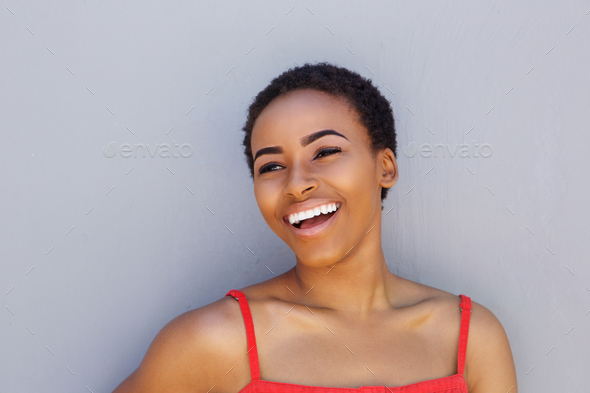 attractive young black woman laughing against gray wall - Stock Photo - Images