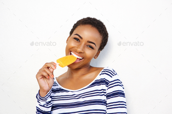 attractive young black woman eating ice cream - Stock Photo - Images