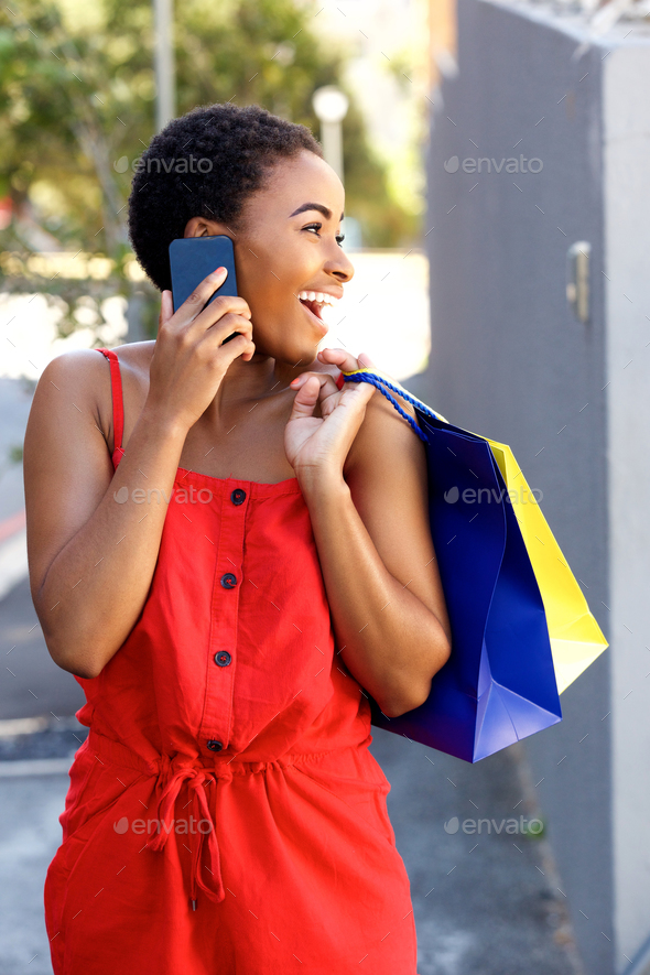 smiling african woman talking on cell phone with shopping bags - Stock Photo - Images