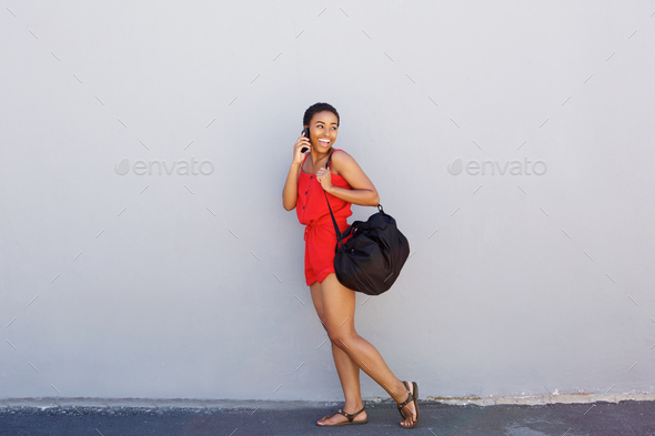 young smiling woman walking and talking on cellphone - Stock Photo - Images