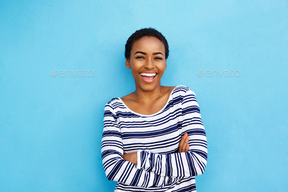 happy young black woman laughing against blue wall - Stock Photo - Images