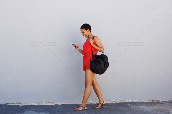 young woman walking and listening to msuic on cell phone - Stock Photo - Images